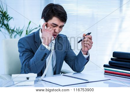 Angry asian businessman on the phone at his office