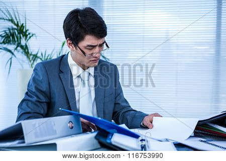 Busy asian businessman at his office