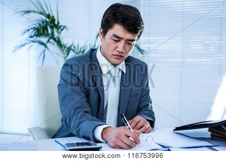 Riled up asian businessman in his desk and writing somethings