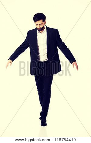 Businessman walking carefully.