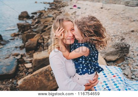 portrait of happy mother and daughter spending time together on the beach on summer vacation. Happy