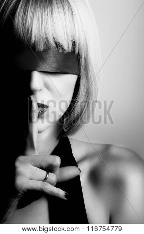Hush-hush. Close up portrait of beautiful sexy young blonde woman raising her finger to red lips sec
