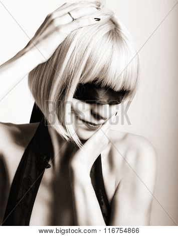 Close up portrait of beautiful sexy young blonde woman  with a bandage on his eyes, puts her hand to