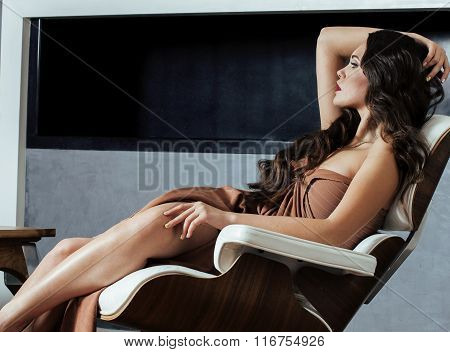 beauty yong brunette woman sitting near fireplace at home, winter warm evening in interior, waiting