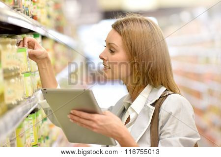 Woman in supermarket checking shopping list on tablet