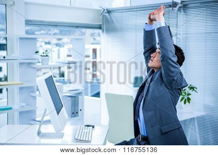 Businessman stretching his arms in his office