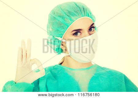 Young woman surgeon doctor shows perfect sign