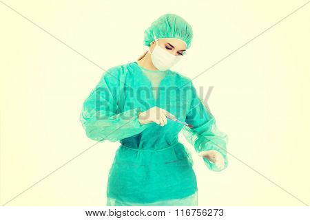 Female surgeon doctor with a scalpel performs the surgery