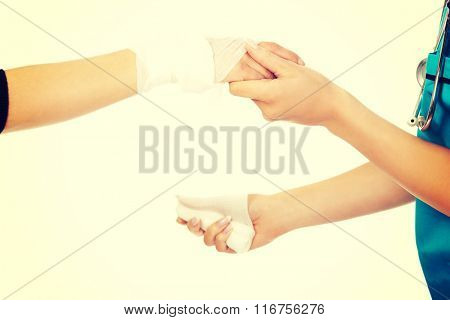 Female doctor bandaging woman hand