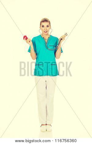 Shocked nurse or female doctor holding stethoscope and heart mod
