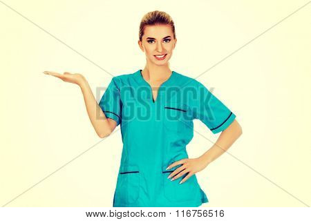 Smiling woman doctor or nurse pointing something