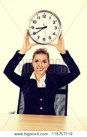 Happy businesswoman with clock behind the desk