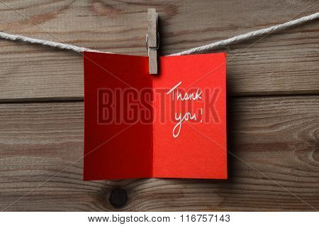 Red Thank You Card Pegged To String On Wood Background