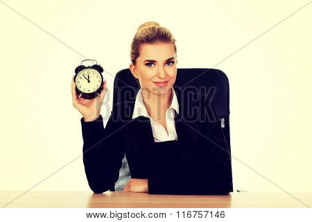 Happy businesswoman with alarm clock behind the desk
