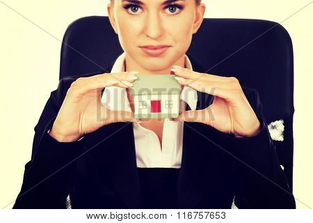 Young smile businesswoman presenting a model house