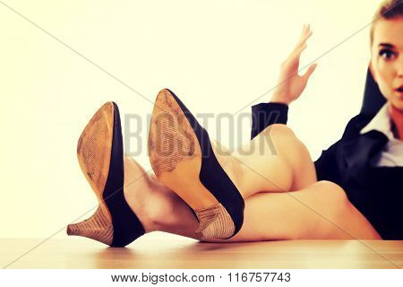 Angry businesswoman holding legs on the desk