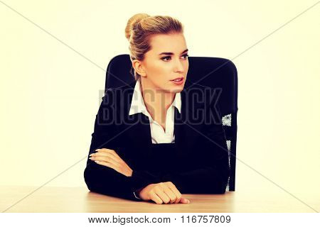 Beautiful worried businesswoman behind the desk