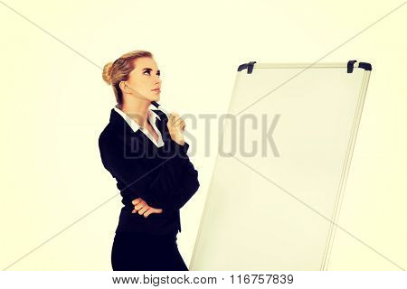 Thinking business woman standing nex to the white board