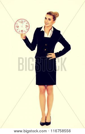 Smile businesswoman holding a big clock