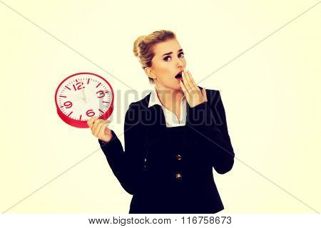 Surprised businesswoman holding a big clock