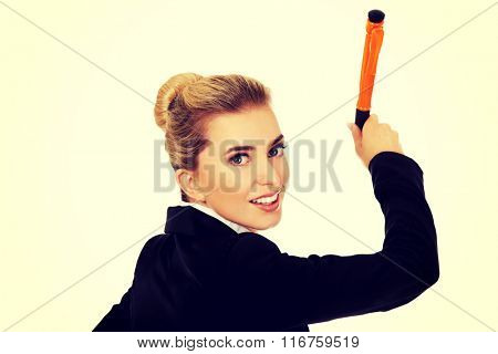 Young businesswoman writes something with big pen