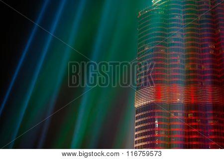 Illuminated building colorful rays on dark background