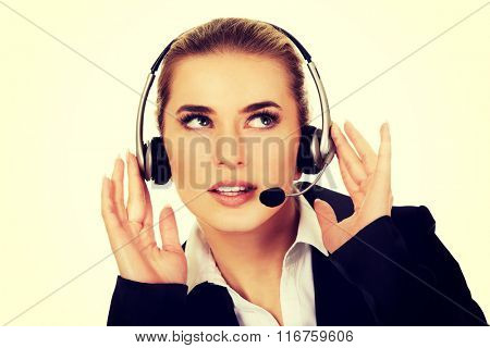 Young woman helpline operator is trying to hear something headphones