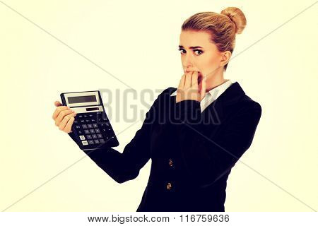 Nervous businesswoman looking at calculator