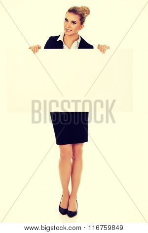 Happy businesswoman holding empty banner.