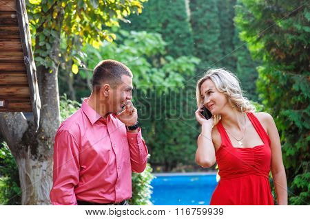 Young Couple In Love Walking In The Park And Talking On The Phone