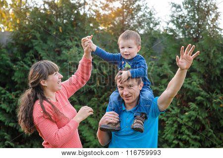 Young Family Walking In Autumn Garden