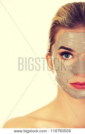 Half face of young woman with facial mask