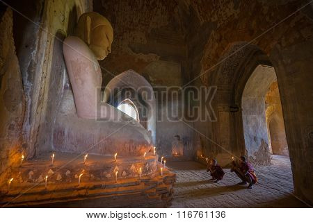 Southeast Asian neophytes light candles inside a Buddihist temple.