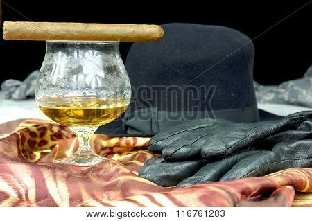 Black Hat On A Brown Scarf With Black Leather Gloves And A Glass Of Cognac And A Cigar