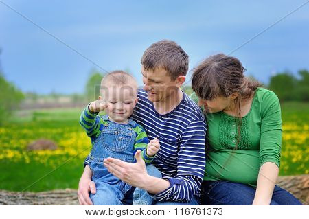 Young Family Walking On The Meadow With Yellow Flowers In Spring