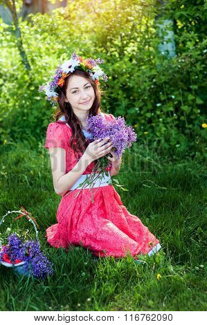 Beautiful Woman In Red Dress Sitting On The Grass With A Branch Of Lilac