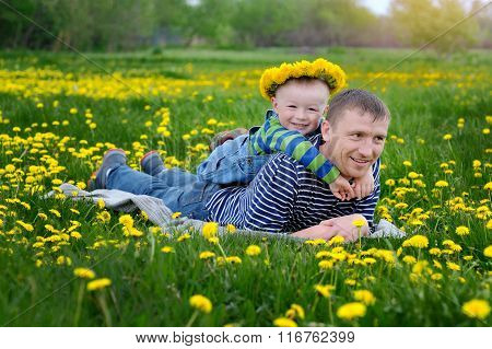 Father And Son On A Meadow In Spring