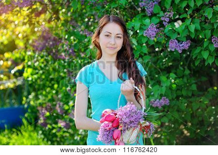 Beautiful Woman With A Bouquet Of Lilacs And Tulips Walking In The Garden