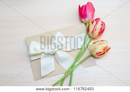 Tulips And Greeting Card With Bow On A Light Background
