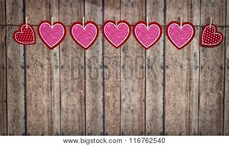 Valentine Hearts Hanging From Twine On A Wooden Background