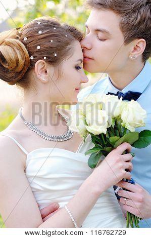 Loving Groom Kissing Bride's Forehead On Wedding Walk