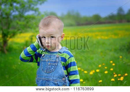 Little Boy Talking On The Phone On A Spring Meadow