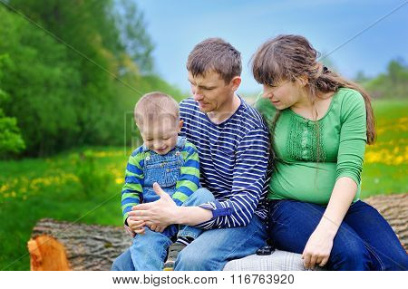 Little Boy With His Parents Sitting On A Tree Stump