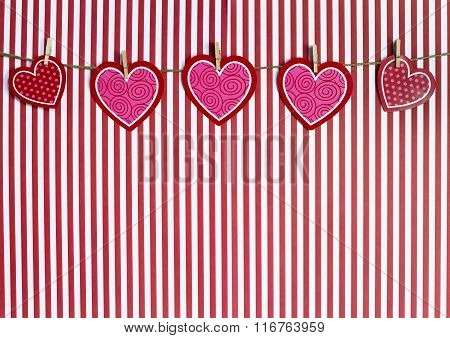 Valentine Hearts Hanging From Twine On A Red Striped Background
