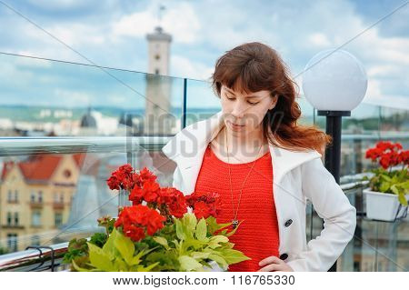 Beautiful Woman In A White Coat Near The Red Flowers In The Background Lviv