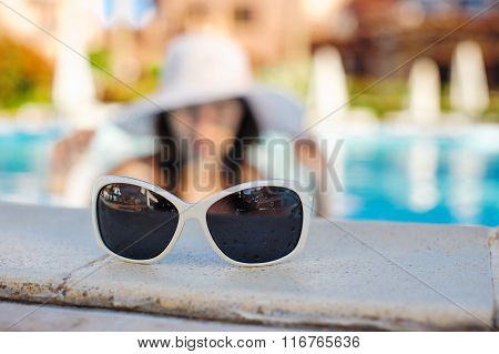 sunglasses in the foreground and the background is blurred woman in the pool