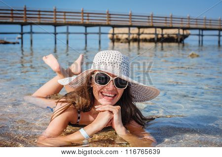 Beautiful Woman In White Hat Lying On The Sea