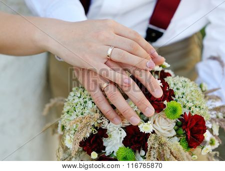 hands of the bride and groom with rings on wedding bouquet