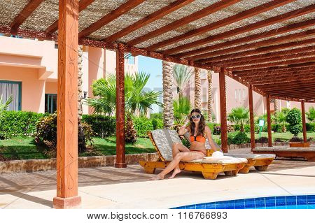 beautiful young woman sitting on a lounger by the pool