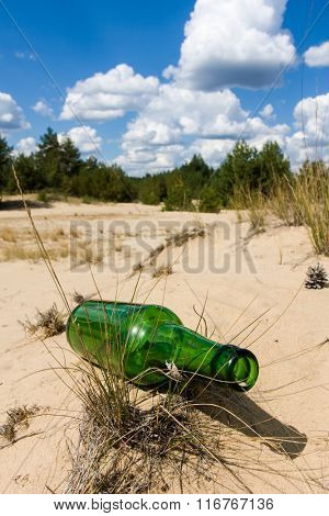 lost green bottle in sand at nice summer day